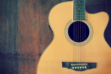 acoustic l guitar with strings on the wooden background