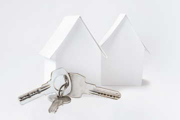 Keys on keyring and two toy paper houses on white background.