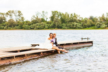 Beautiful bride and groom by a lake or river