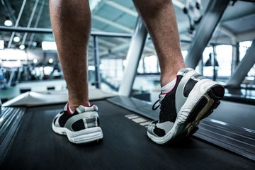 Cropped image of muscular man using treadmill