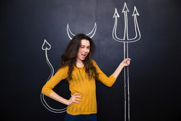 Flirty woman standing and winking over chalkboard background