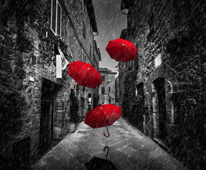 Fotomurales - Umrbellas flying with wind and rain on dark street in an old Italian town in Tuscany, Italy