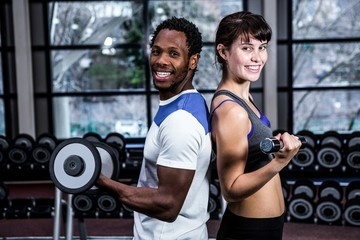 Fit couple lifting dumbbells back to back