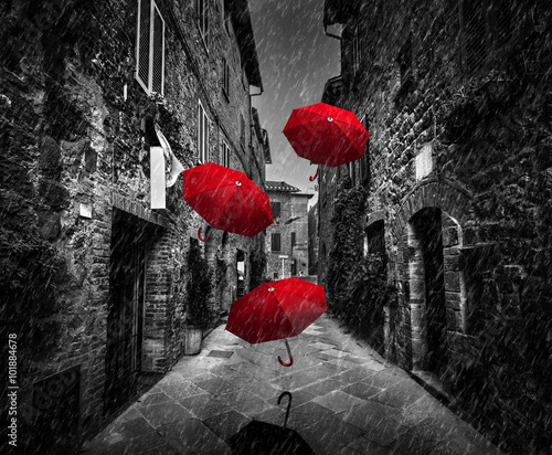 Fototapete Umrbellas flying with wind and rain on dark street in an old Italian town in Tuscany, Italy