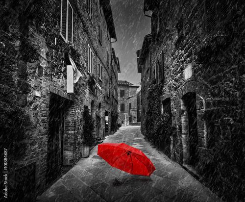 Fototapete Umbrella on dark street in an old Italian town in Tuscany, Italy. Raining.