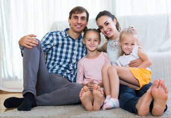 Family values: portrait of parents with little girls indoors