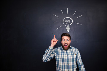 Excited man pointing up over blackboard background with light bulb