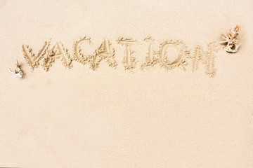 """""""VACATION"""" written in the sand on the beach with copy space for"""