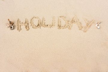 """HOLIDAY"" written in the sand on the beach with copy space for t"
