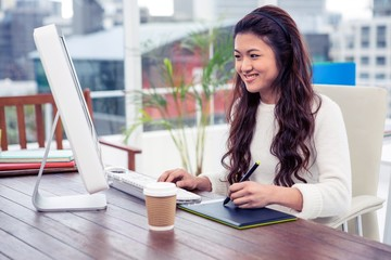 Smiling Asian woman using digital board and computer