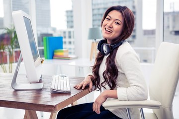 Smiling Asian woman with headphones around neck