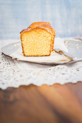 Sliced homemade orange cake on silver tray. Selective focus.