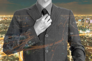 Double exposure of young businessman on night city background.