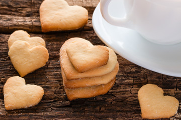homemade cookies in the shape of heart and white cup on a wooden background