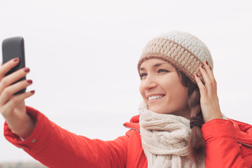 Young woman using smart phone outdoors in winter