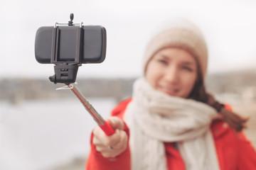Woman using phone on selfie stick