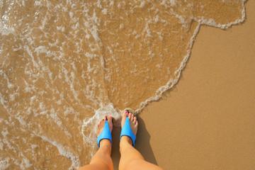 foot in flip flops on the beach