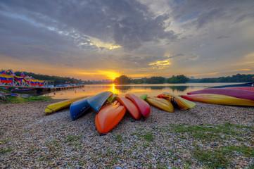 Colorful kayaks with sunset at the background