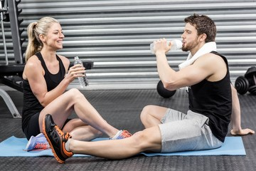 Couple sitting on fitness mat