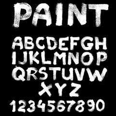 Hand-drawn font on textured paper with paint strokes on black ba