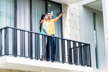 Indian woman and man standing on balcony of house