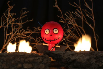 Halloween Devil Doll on black background with dead trees and fire.