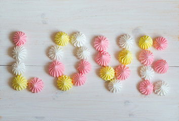 Inscription love meringue made of pastel colors on a white woode