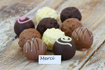 Merci (thank you in French) card with assorted chocolates on rustic wooden surface
