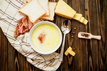 cheese soup with smoked pork ribs , potatoes, carrots , peppers , spices and bread on the wooden background