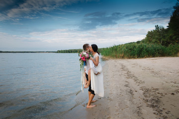 Young handsome groom holds his bride in his arms on the beach with a big bouquet of beautiful flowers, lifestyle, concept, love, tenderness