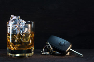Whiskey glass and car keys on dark rustic wood, concept alcohol
