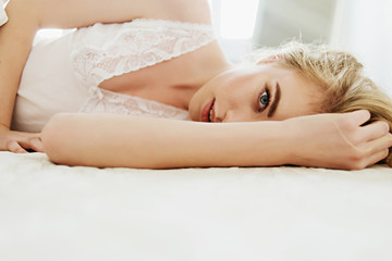 Portrait of a beautiful blonde girl lying on a white bed