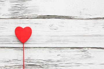 Red wooden heart on white wooden desk background.