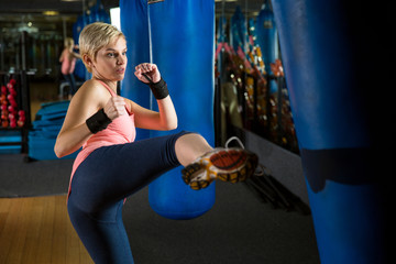 Cute woman innocent look learning self defense kicking bag in gym class fists