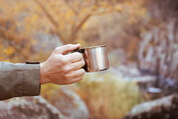 Man holding a mug of hot drink on cliff edge in Autumn