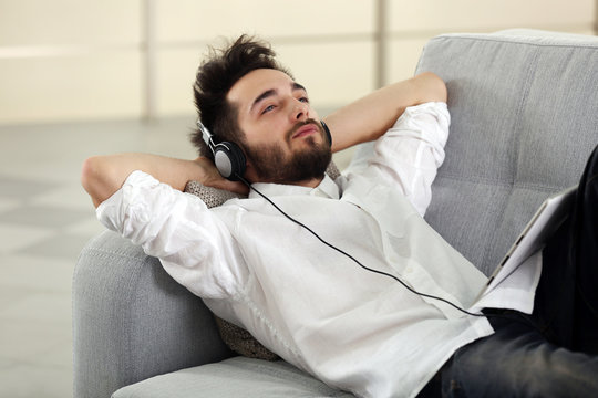 Young man listens music with headphones on grey sofa in the room