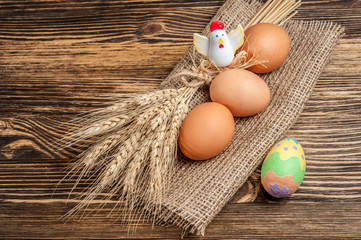 there are three eggs on sackcloth with wheat spica, with chiken decorated