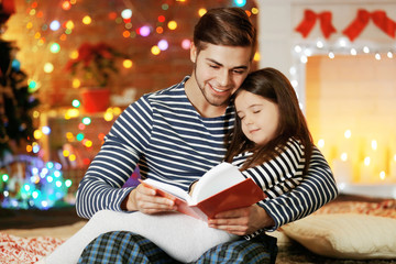 Older brother with little sister reading fairy tale in Christmas living room