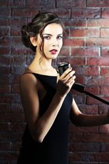 Portrait of attractive singing woman  on brick wall background, close up