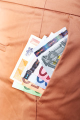Euro money in pocket of brown pants closeup