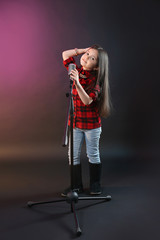 Beautiful little girl with microphone on dark purple background