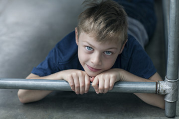 Child lying down on floor looking at camera