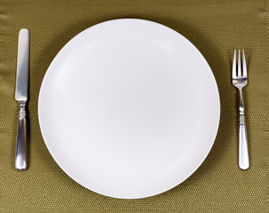 Simple white plate with silverware for dinner setting