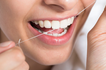 Woman Flossing Teeth At Home