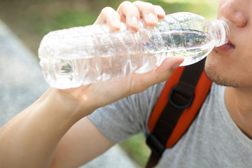 Close up of man drinking mineral water from bottle in the park - health care concept