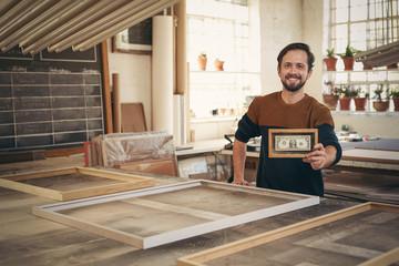 Entrepreneur holding up a framed bank note in his workshop
