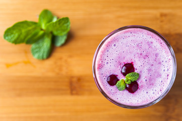 Glass of homemade smoothie with cherry and mint leaves on wooden table. Conception of healthy food.  Nonalcoholic drinks.