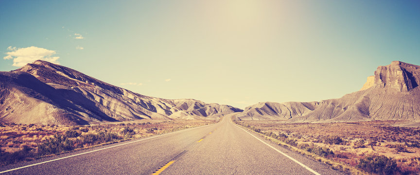 Vintage toned panoramic photo of desert road, Utah, USA