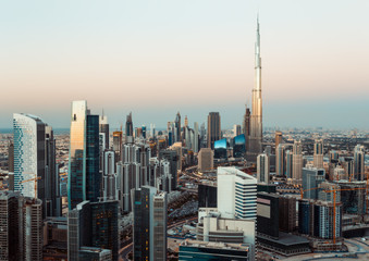 Fantastic roofftop view of Dubai's business bay towers at sunset. Modern architecture and travel background.