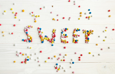 Word Sweet written by little colorful candies on white wooden ba